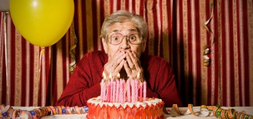 B4FGHX Astonished old grandmother lost her dentures while she try to blowing out the candles on the cake for her birthday. Image shot 2008. Exact date unknown.